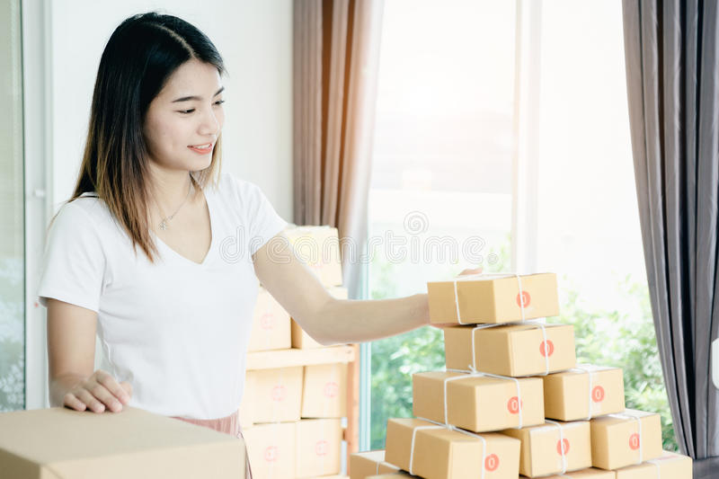 Young asian girl is freelancer. With her private business at home office, working with laptop, coffee, online marketing, Customer order and packaging or packing royalty free stock photo