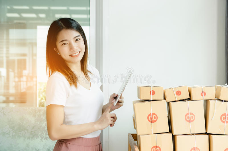 Young asian girl is freelancer. With her private business at home office, working with laptop, coffee, online marketing, Customer order and packaging or packing royalty free stock image