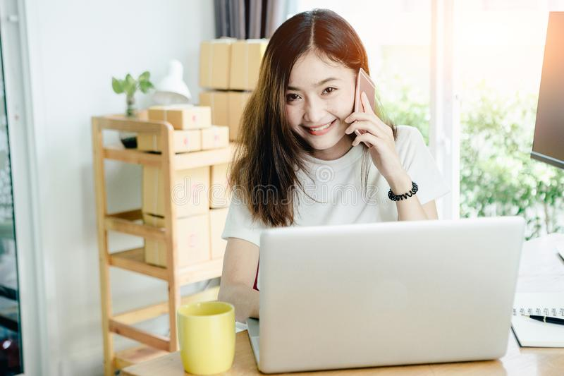 Young asian girl is freelancer with her private business. At home office, working with laptop, coffee, online marketing. Customer Support stock photo