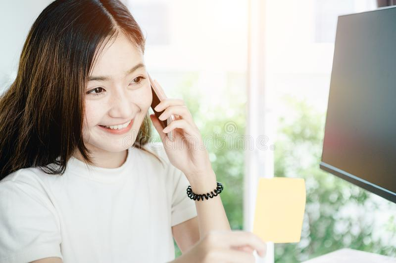 Young asian girl is freelancer with her private business at home office. Working with laptop, coffee, online marketing. Customer Support royalty free stock photo