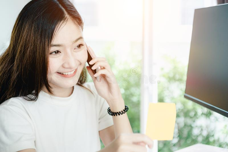 Young Asian girl is freelancer with her private business. At home office, working with laptop, coffee, online marketing. Customer Support royalty free stock image
