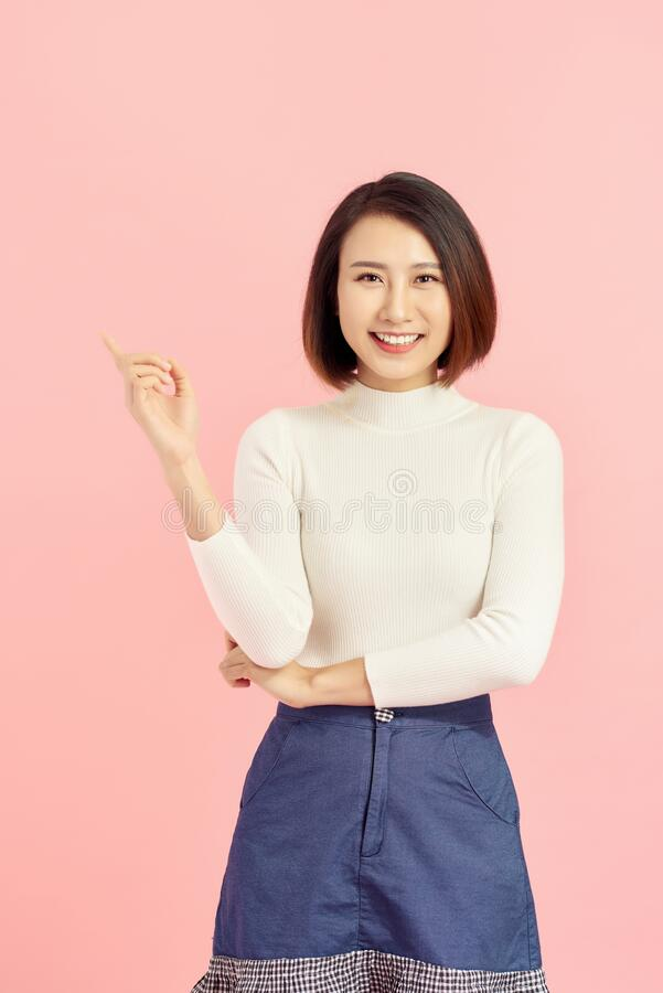 Young Asian girl have good idea. Happy smiling woman isolated on pink background. Copy space stock photos