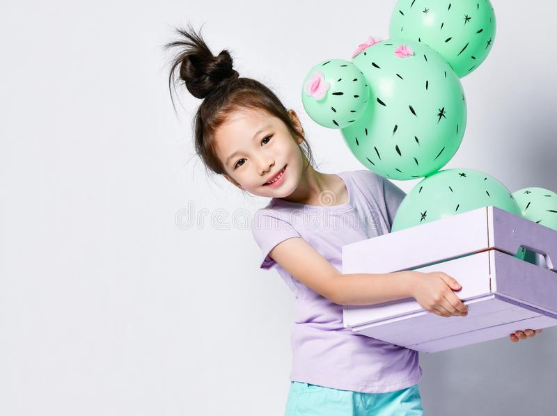 Young asian girl hold cactus balloon in pastel pink and purple flower box made of green round balloons with pink flowers royalty free stock photos