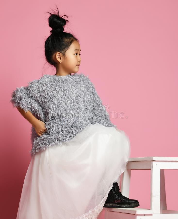 Young asian girl kid in long white skirt, grey fluffy sweater and black shoes with foot on the step stock photography