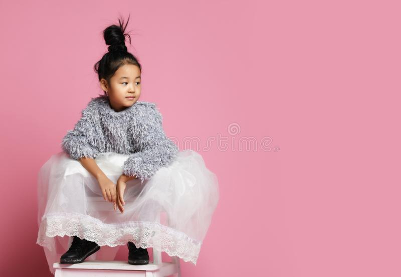 Young asian girl kid in long white skirt, grey fluffy sweater and black shoes sitting and looking the direction the text stock photos