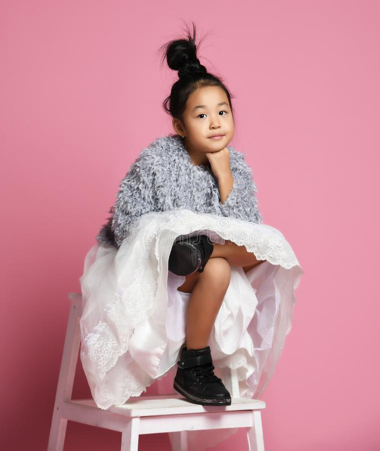 Young asian girl kid in long white skirt, grey fluffy sweater and black shoes slegs crossed and looks at you stock photo