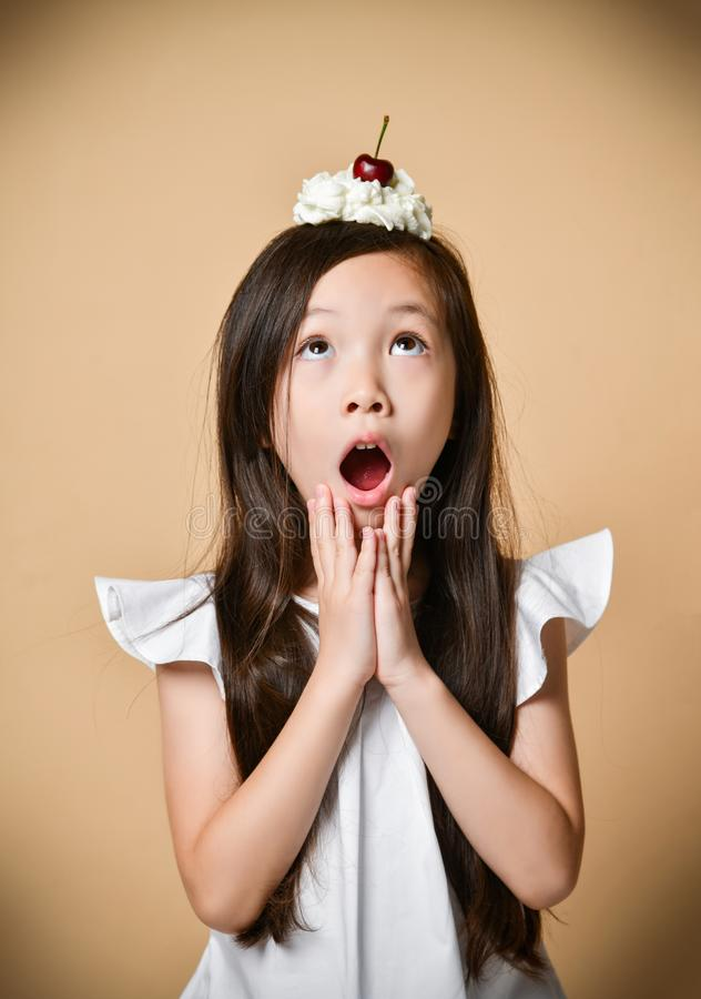 Young asian girl kid with sweet cherry dessert on head on a beige stock photo