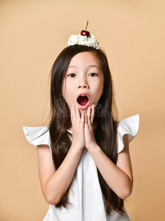 Young asian girl kid with sweet cherry dessert on head on a beige royalty free stock image
