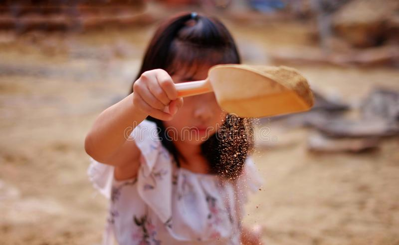 A young Asian girl playing in a sandbox, sprinkling sand from a small shovel. A cute young Asian girl playing in a sandbox, sprinkling sand from a small shovel stock images