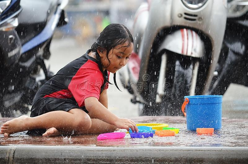 Young Asian girl selects a toy as she plays in the rain during monsoon season in Thailand. stock images