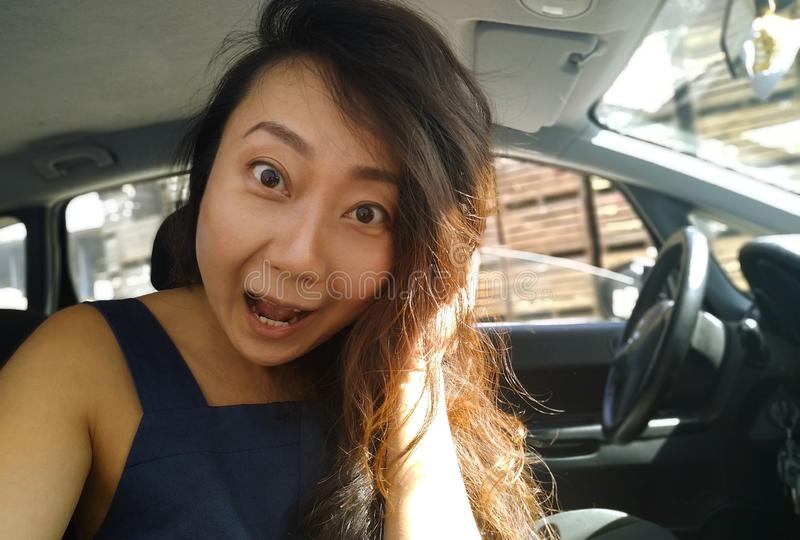 Young asian girl sitting inside of a car and surprised looking at camera. Young happy asian girl sitting inside of a car and surprised looking at camera royalty free stock image