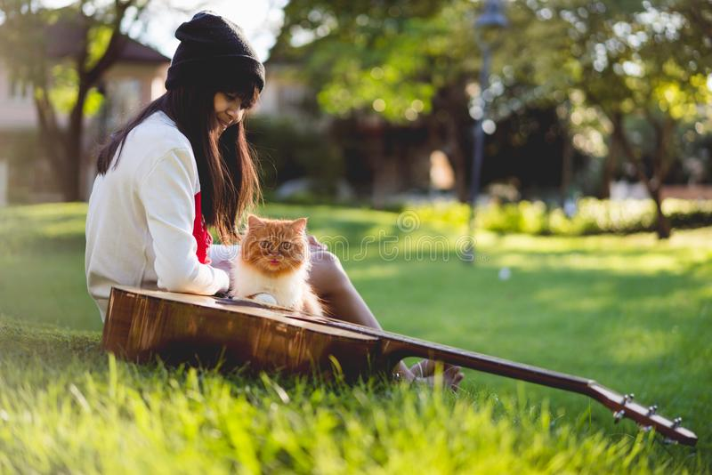 Dreaming. Young asian girl sitting in the park with her kitten and dreaming stock photos