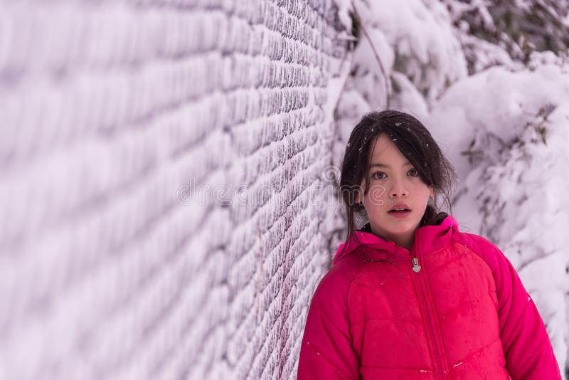 Young Asian girl standing next to snow covered fence royalty free stock photos