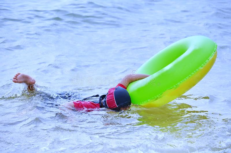 Young Asian girl swimming in ocean while looking underwater with her goggles. Using her blowup donut to keep her afloat this young Thai girl looks underwater royalty free stock photos