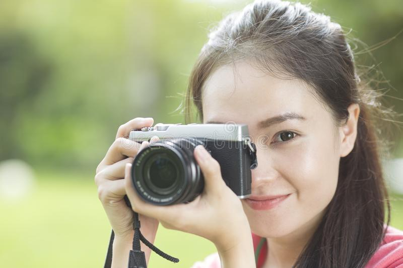 Young asian girl taking photo outdoors with digital camera royalty free stock photos
