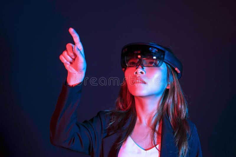 Young asian girl try augmented and virtural reality glasses hololens in the lab room. Mixed reality future technology concept stock images