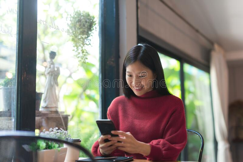 Young Asian girl using phone at a coffee shop .Woman happy on smartphone in cafe. royalty free stock photography
