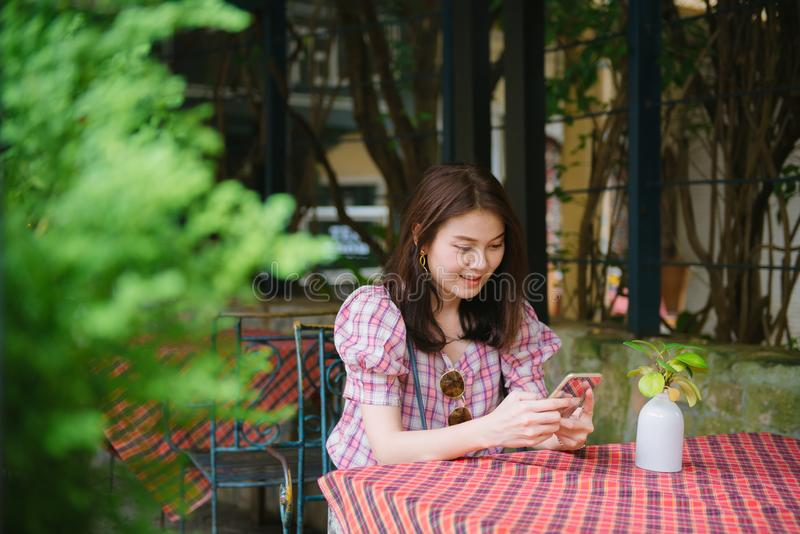 Young asian girl using smartphone waiting for her friend to come at restaurant. royalty free stock photography