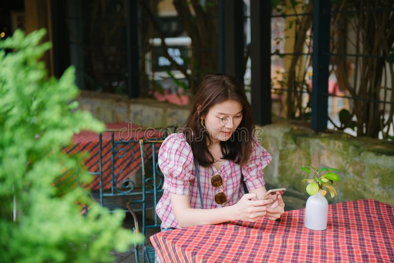 Young asian girl using smartphone waiting for her friend to come at restaurant. stock photos