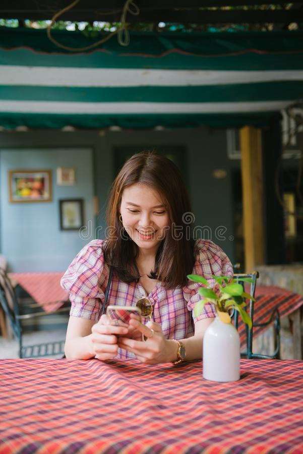Young asian girl using smartphone waiting for her friend to come at restaurant. royalty free stock image