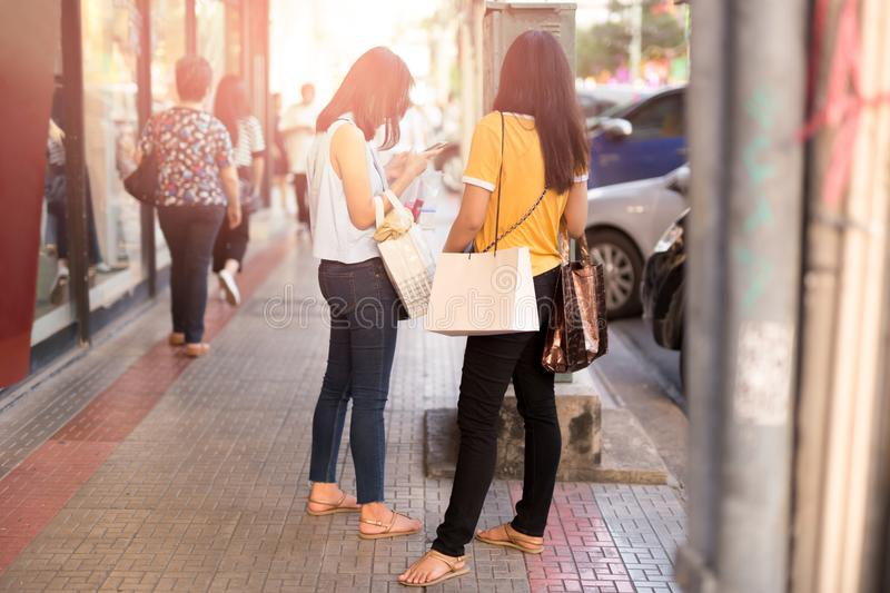 Young asian girls holding shopping bags using cell phone stock images