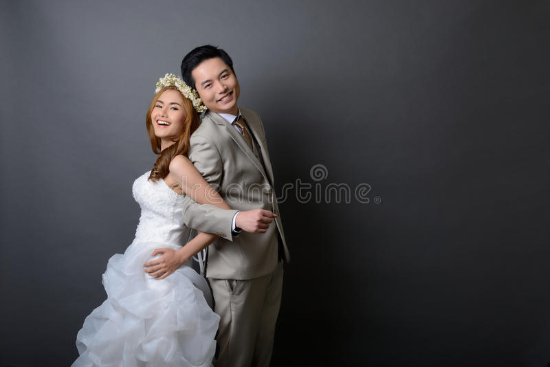 young asian groom and bride posing and smiling in studio for pre wedding shot. royalty free stock images