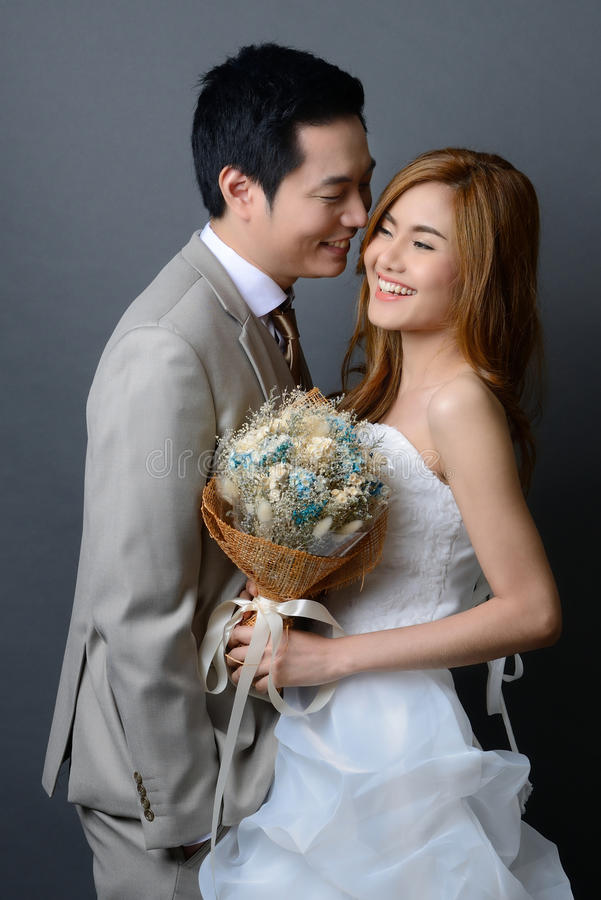 Young asian groom and bride posing and smiling in studio for wed stock images