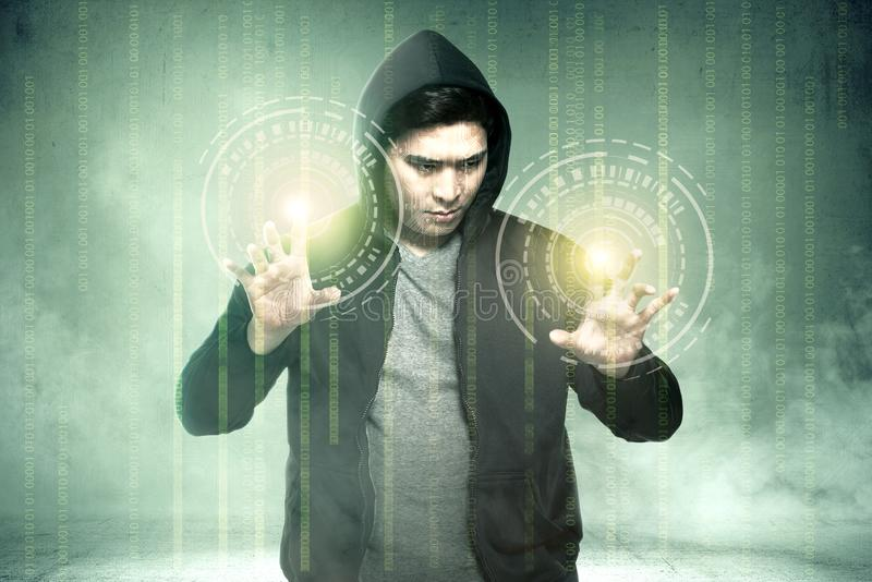 Young asian hacker in black hoodie touching virtual screen with binary code. Over green background royalty free stock photo