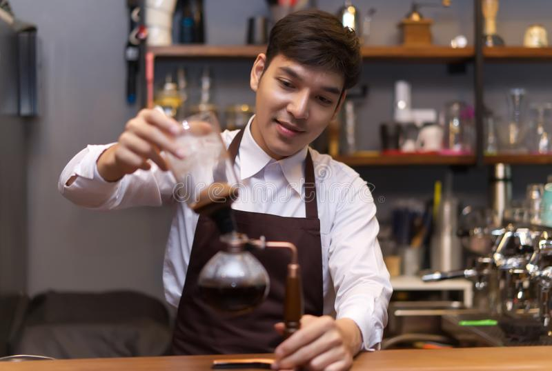 Young Asian Handsome caucasian barista pouring coffee with Siphon vacuum coffee maker. Startup Samll Business Concept. stock photo