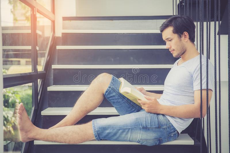 Young asian handsome man reading book for relax at home, male activities for leisure. Education success concept stock images
