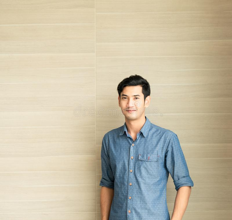 Young asian handsome man who is wearing a blue shirt casual wear is standing in front of wooden wall in office  morning time. Lifestyle portrait royalty free stock photo