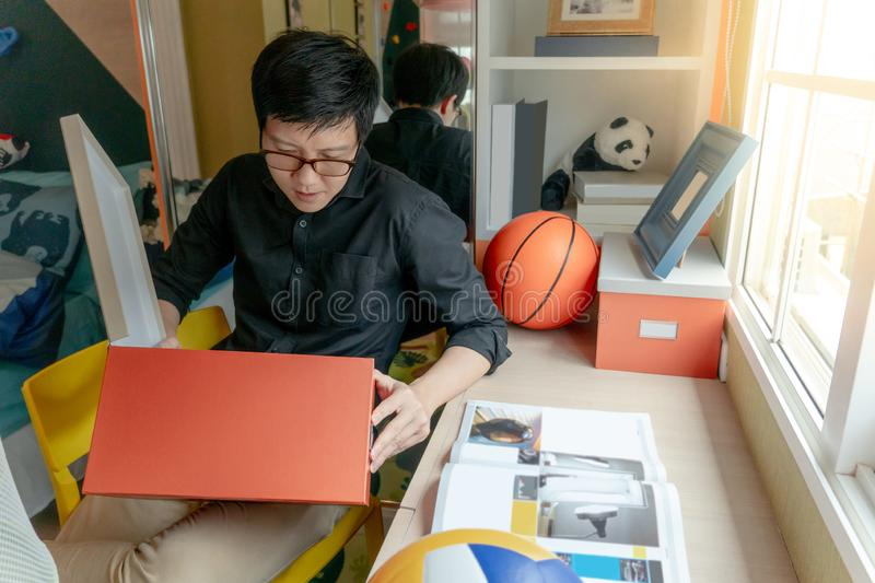 Asian man opening box sitting in bedroom. Young Asian happy man with eyeglasses opening orange paper box sitting in bedroom. Home living lifestyle concept royalty free stock photos