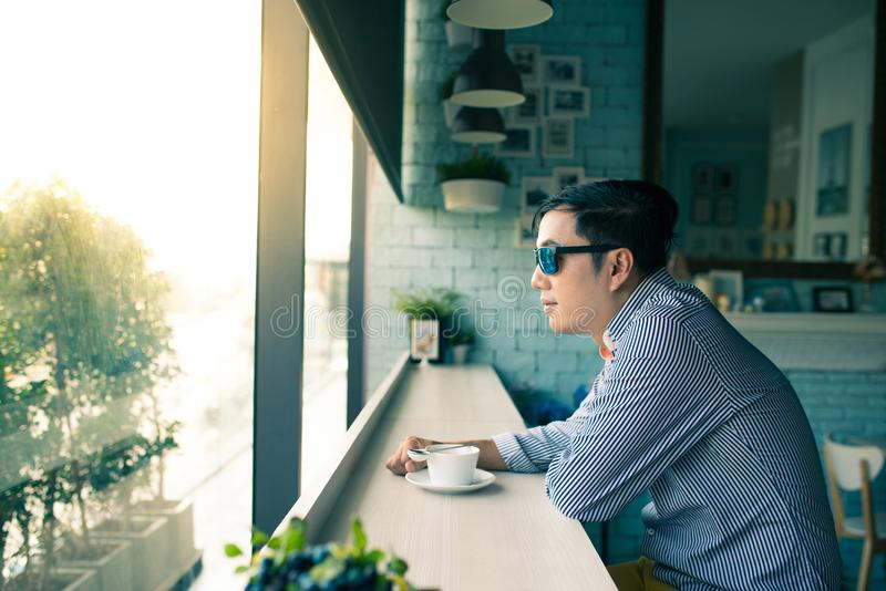 Young Asian happy man look through clear window and thinking during coffee time in cafe, casual freelance lifestyle or digital no. Mad concepts royalty free stock photos