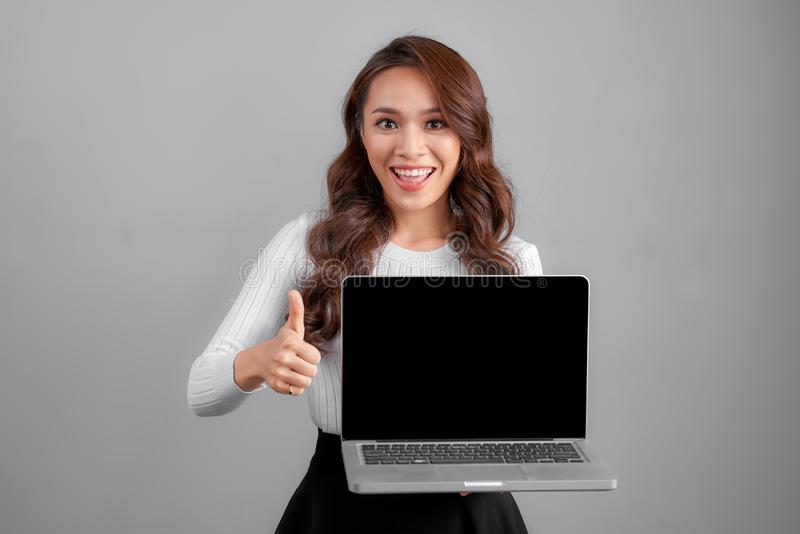 Young Asian happy woman with notebook laptop isolated on gray background stock photography