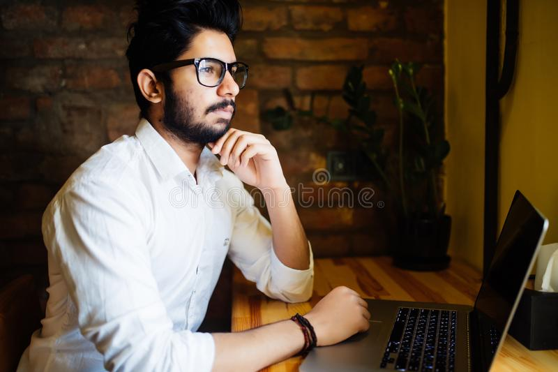 Young Asian Indian businessman using a laptop during office break at cafe, relaxing with a cup of coffee. royalty free stock photo