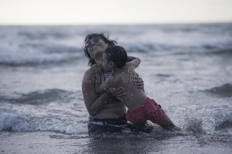 Young Asian Indonesian mother and little son enjoying summer holidays having a bath on the sea at tropical beach in family. Lifestyle candid portrait of young royalty free stock images
