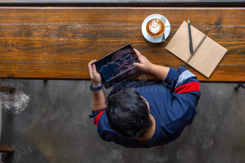 Young Asian investor tracking stock market trading graph on tablet. Young Asian investor tracking stock market trading graph at coffeeshop stock images