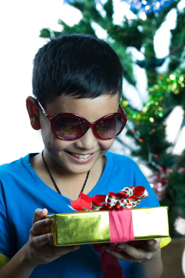 Young asian kid on sunglass look at his Christmas present royalty free stock photo