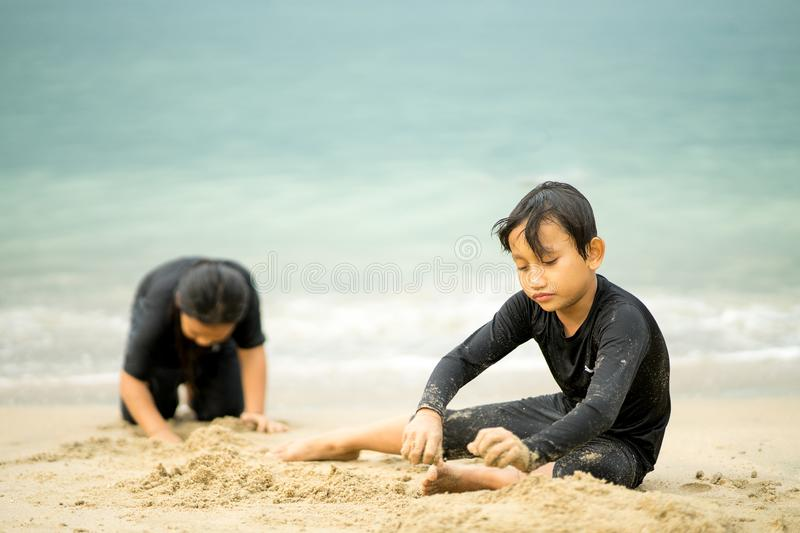 Young asian kids are playing on the beach. royalty free stock photo