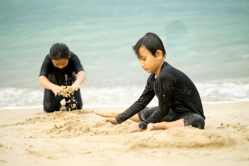 Young asian kids are playing on the beach. royalty free stock photography