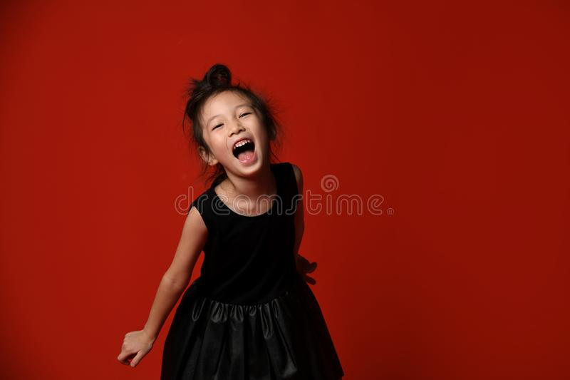 Young asian Korean girl in black trendy dress happy shouting screaming on red stock photo