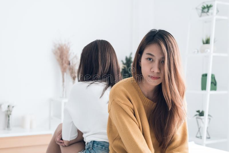 Young Asian lesbian couple argue and turn their back to each other in the period of sad in the bedroom. LGBT couple sulky to another in the bedroom with a sad royalty free stock photo