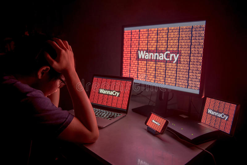 Young Asian male frustrated by WannaCry ransomware attack. Young Asian male frustrated, confused and headache by WannaCry ransomware attack on desktop screen stock image