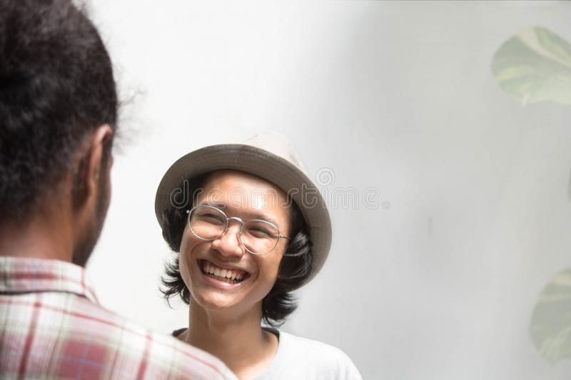 Young asian male hand shake with friend as foreground, young asian man with glasses handshake with black man royalty free stock photos
