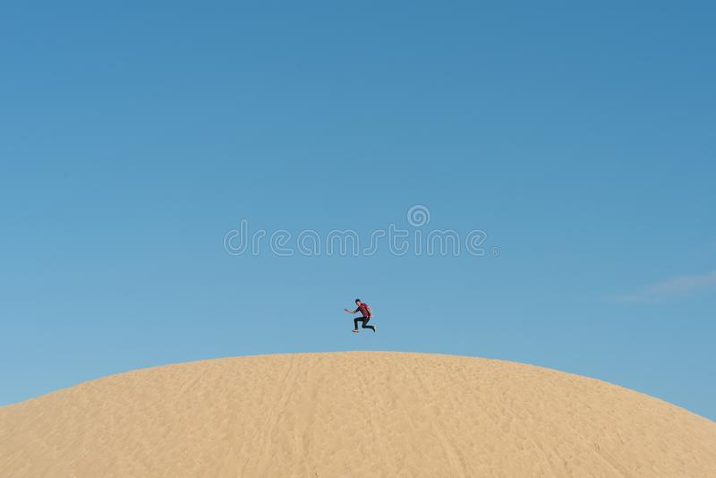 Young asian male jumping high on a sand dunes against clear blue sky stock image