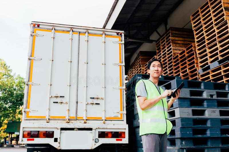 Young Asian male logistics warehouse distribution business entrepreneur using a digital tablet. Young Asian male logistics warehouse distribution business royalty free stock photo