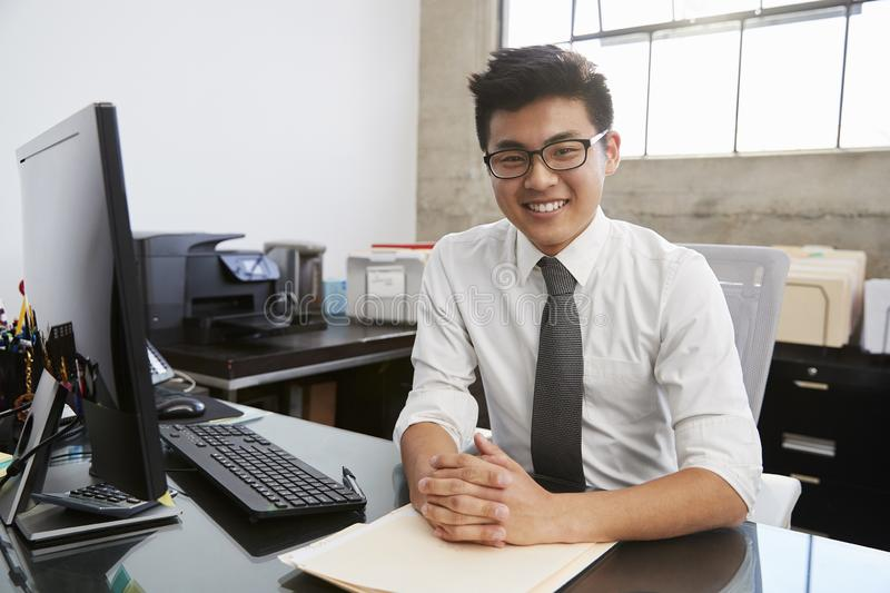 Young Asian male professional at desk smiling to camera royalty free stock images
