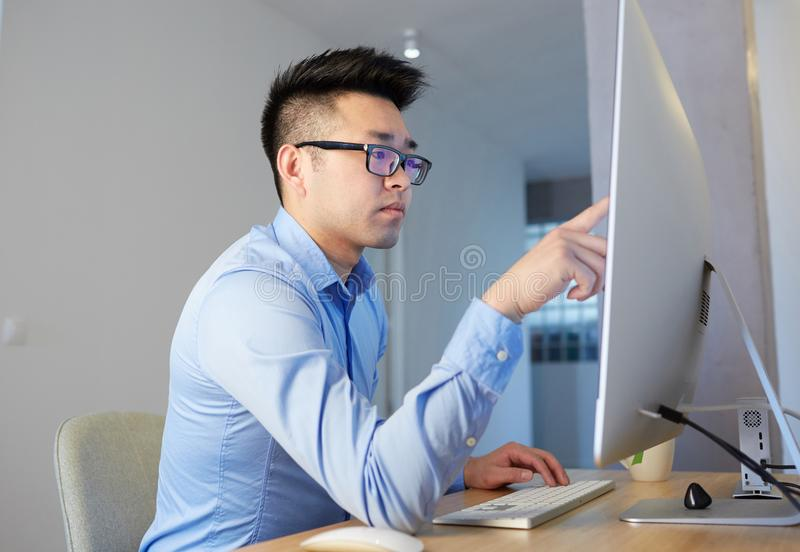 Young asian male programmer wearing shirt and glasses working while sitting in front of desktop computer at coworking stock photos