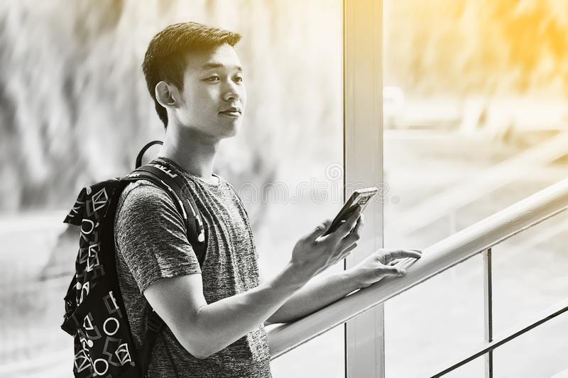 Young asian male student with smartphone in hand wearing a t-shirt and a backpack standing on university stairs and royalty free stock image