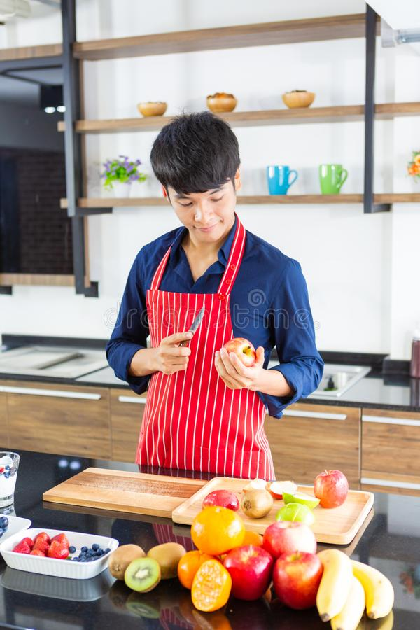 Young asian man with apron cutting red apple and assorted fruits royalty free stock photography